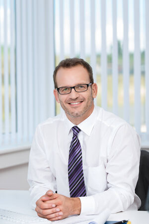 shirtsleeves: Confident friendly businessman wearing glasses sitting at his desk in the office in his shirtsleeves smiling at the camera Stock Photo