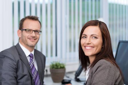 Affaires confiant amical avec un beau sourire motivés assis dans son bureau avec un collègue masculin