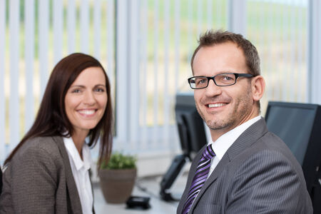 Successful friendly businessman wearing glasses sitting in the office having a meeting with a female coworker smiling at the camera photo