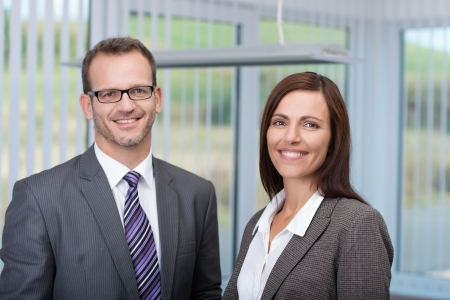Smiling business partners with a successful confident man and woman posing side by side in the office smiling at the camera