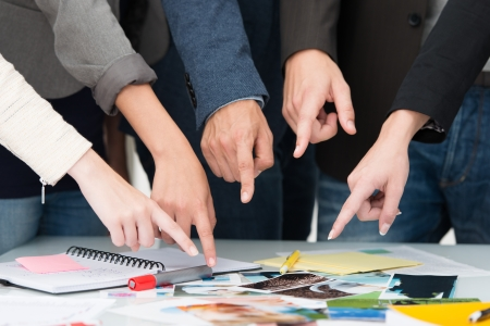 teamwork hands: Cropped view of the hands of a group of people in a business team pointing to a universal choice of photos and paperwork displayed on a table Stock Photo