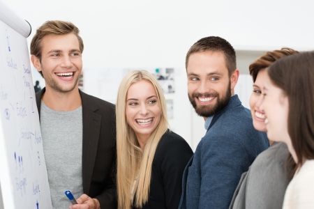 Happy laughing group of diverse young professional businesspeople standing together in front of a flip chart during a meeting or presentation