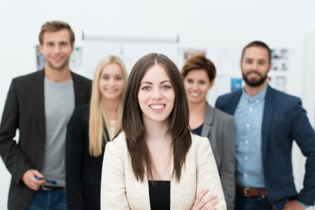 comprising: Successful female team leader with a warm friendly smile standing with folded arms in front of the four professional business people comprising her team