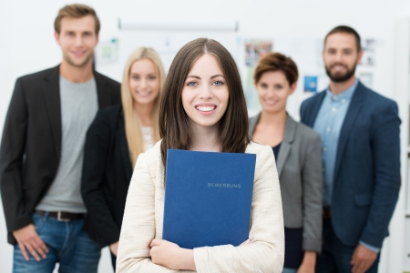 Attractive smiling young businesswoman holding her curriculum vitae in a blue folder as she stands waiting for a job interview with other diverse applicants in the background Stok Fotoğraf