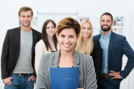 work material: Group of job applicants with a smiling confident young woman in the foreground holding her Curriculum vitae in her hands
