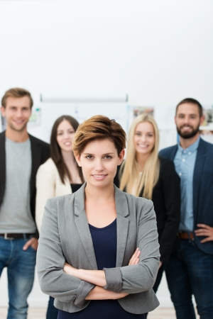 Successful manageress or team leader standing in front of her colleagues with folded arms smiling at the camera