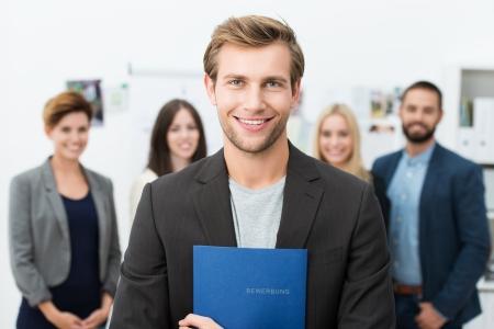 entrevista de trabajo: Exitosa sonriente joven solicitante de empleo masculina que sostiene una carpeta azul con su curriculum vitae que presenta delante de sus nuevos compa�eros de trabajo o equipo de negocios Foto de archivo