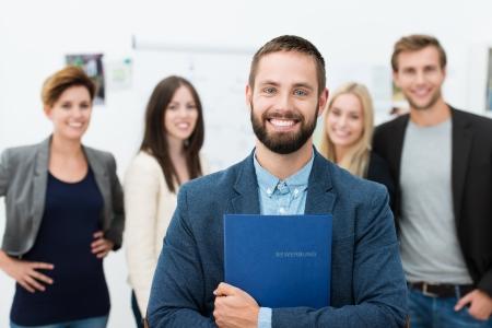 Confiado hombre de negocios feliz sosteniendo un archivo que contiene su curriculum vitae en el pecho radiante ampliamente de emoción mientras se pone delante de sus compañeros de trabajo o equipo de negocios