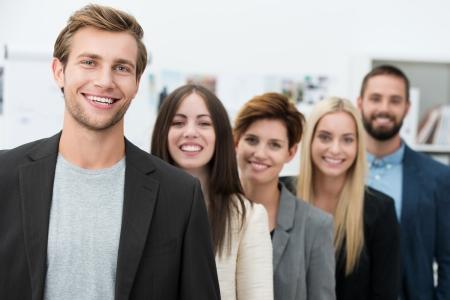 多様な若いプロ男女のハンサムな若いチームの指導者が率いる後退列に並んで立って幸せな独創力のあるビジネス チーム