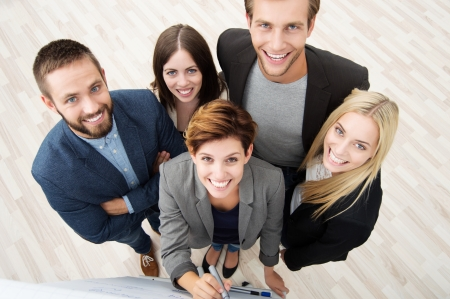 Group of five diverse young business people viewed high angle looking up at the camera as they stand at a flipchart having a discussion photo