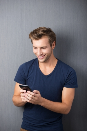 beaming: Excited handsome young man reading an sms message on his mobile phone with a beaming smile