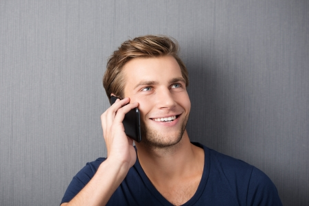 Young man chatting on a smartphone smiling with pleasure as he listens to the conversation, against a green studio background photo
