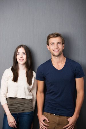 standing against: Attractive thoughtful young couple standing side by side against a clean blackboard with copyspace staring up into the air Stock Photo