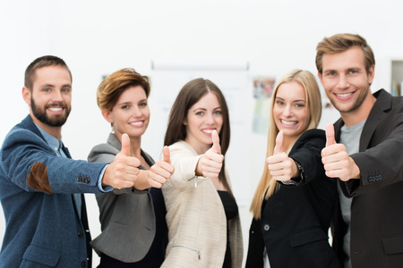 office women: Motivated successful business team of diverse young professionals giving a thumbs up to show their agreement and support or to indicate a victory Stock Photo