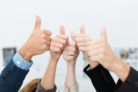 Successful diverse young business team giving a victorious thumbs up to show their success and motivation, close up view of their raised hands photo