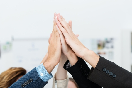 partner: Conceptual image of teamwork and cooperation with a group of business people raising their hands and placing them together, close up view of their hands