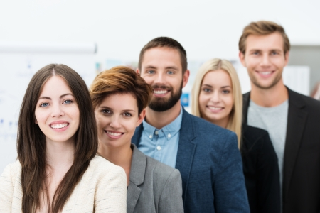 start up: Conceptual image of team leadership with a group of professional successful young business men and women standing in a line headed by two attractive smiling businesswomen