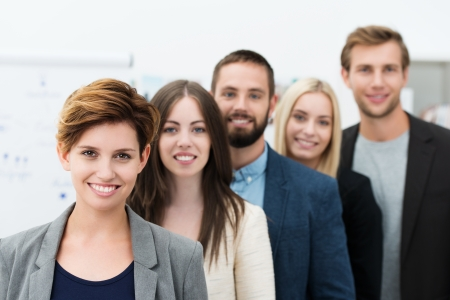 Group of young business people lead by a pretty confident young woman team leader with a friendly smile Stock Photo