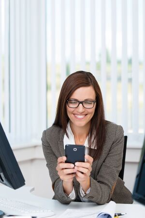 Happy and smiling business woman sitting at her desk and using a smartphone photo