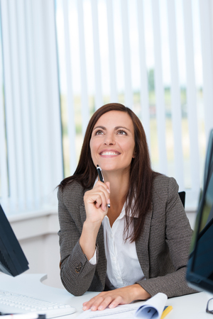 perceptive: Happy businesswoman looking up with an expression of remembrance sitting at the desk in the office