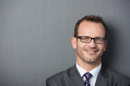 Close-up portret van een vriendelijke zakenman leunend tegen een grijze muur met exemplaar-ruimte aan de linkerkant