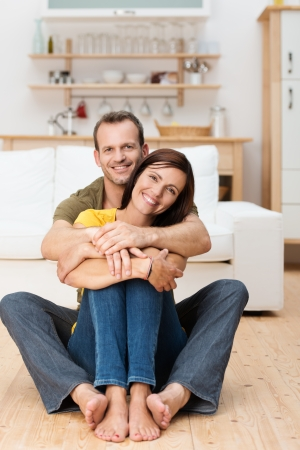 Portrait of a happy loving adult couple sitting on the floor of their house with the man embracing the woman from behind photo