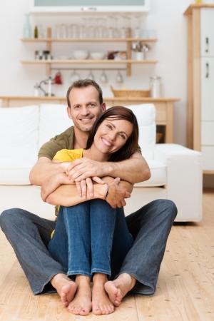 mujer de espaldas: Retrato de una pareja de adultos amorosa feliz, sentado en el piso de su casa con el hombre abrazando a la mujer por detr�s Foto de archivo