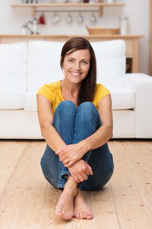 mujeres elegantes: Mujer adulta feliz sentado en el piso de su casa con los brazos alrededor de las rodillas
