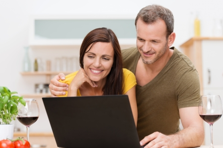 woman searching: Attractive young couple using a laptop in the kitchen as they enjoy a glass of wine and orange juice together smiling as they read information on the screen