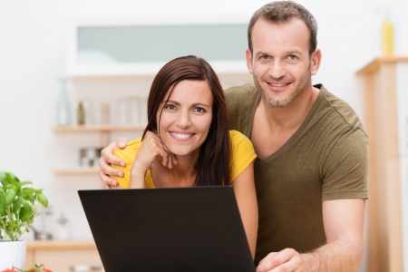 woman searching: Friendly attractive young couple working on a laptop together in the kitchen or living room posing together arm in arm smiling for the camera