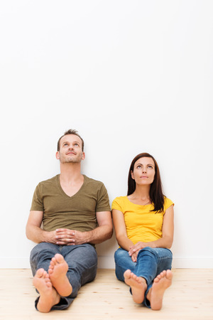 Thoughtful barefoot young couple sitting side by side on the wooden floor in the living room looking up at they ceiling contemplating the move to their new house photo