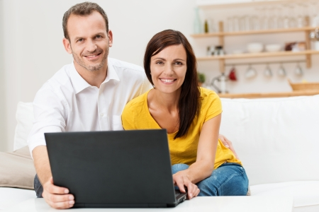 Smiling attractive young couple using a laptop computer sitting together in their living room on the sofa photo