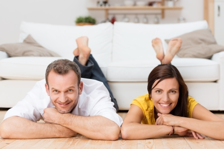 two floors: Happy relaxed couple smiling at the camera as they lie on their stomachs on the wooden floor in their living room with their feet on the sofa