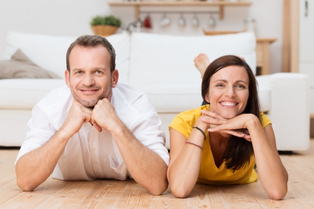unwinding: Lazy attractive young couple unwinding at home lying on their stomachs on the wooden floor in the living room grinning at the camera