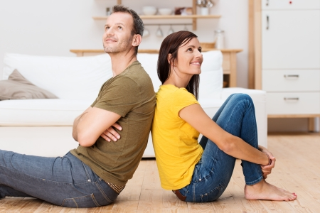 Young couple relaxing on the floor at home sitting barefoot back to back each looking up into the air with a thoughtful smile as they plan their future together photo