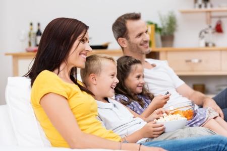 familien: Gl�ckliche junge Familie vor dem Fernseher mit attraktiven jungen Eltern sitzen mit ihren beiden Kindern auf einem Sofa im Wohnzimmer lachend auf dem Programm Lizenzfreie Bilder