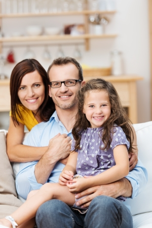 young man portrait: Pretty little girl with a beaming smile sitting on a sofa with her proud parents in a close embrace as they pose for a family portrait