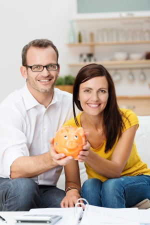 bank: Enthusiastic attractive young couple planning for the future sit side by side on a sofa in the living room holding a piggy bank with an open file and calculator in front of them