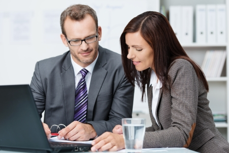 succesful: Succesful male and female business partners having a discussion seated at a desk in the office together analysing some paperwork