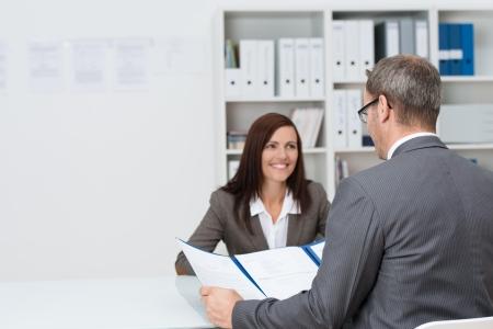occupation: Zaken man die een sollicitatiegesprek met een aantrekkelijke jonge vrouwelijke kandidaat zat tegenover hem aan de balie in het kantoor beantwoording van zijn vraag met betrekking tot haar CV