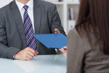 job occupation: Employment interview with a close up view of a female applicant handing over a file containing her curriculum vitae to the businessman conducting the interview