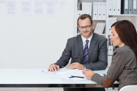 Business man and woman in a meeting in the office sitting at a table discussing paperwork with copyspace alongside photo