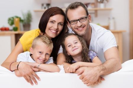 Liefhebbende ouders met hun zoontje en dochter poseren samen voor een portret leunend over de rug van een grote bank in de woonkamer