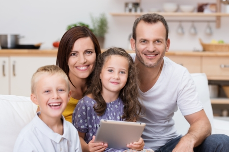 Happy young family relaxing with a tablet-pc with a young brother and sister and their two attractive young parents posing together in the living room photo