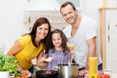 preparing food: Cute young girl cooking with her parents in the kitchen as the three pose with broad smiles alongside the stove and spaghetti ingredients Stock Photo