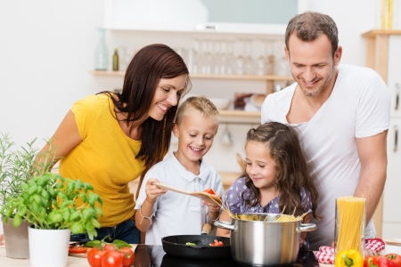 Happy young family with Mum, Dad and two young children cooking in the kitchen preparing a spaghetti meal together Stock Photo
