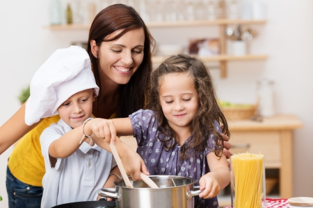 prepare: Small brother and sister cooking a meal both stirring the contents of the same pot watched over by their laughing young mother
