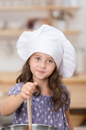 Cute little girl in a white chefs toque standing in the kitchen holding a wooden spoon in a large saucepan photo