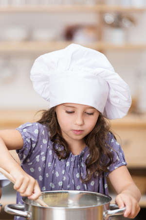 Cute little girl in a chefs toque cooking in the kitchen standing over a large stainless steel pot stirring the contents photo