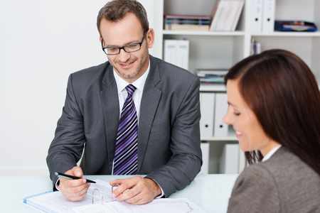 Business partners at work in the office with focus over the shoulder of a woman to a smiling confident businessman in glasses working on paperwork photo